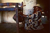 Yemen, wadi moor,grandmother cradles her grandchild i a rustic baby cot