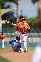 Baltimore Orioles second baseman Alejandro Juvier (28) throws to first as Brandon Lowe (5) slides in and shortstop  Irving Ortega (1) looks on during an Instructional League game against the Tampa Bay Rays on September 19, 2016 at Ed Smith Stadium in Sarasota, Florida.  (Mike Janes/Four Seam Images)