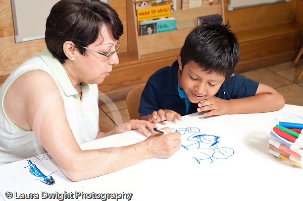 Education Preschool 3-5 year olds art activity  female teacher talking with boy about his drawing and writing down his words horizontal