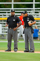 Umpires Brad Polk (left) and Ronnie Whiting talk between innings of the Appalachian League game between the Greeneville Astros and the Burlington Royals at Burlington Athletic Park on July 1, 2013 in Burlington, North Carolina.  The Astros defeated the Royals 7-0 in Game One of a doubleheader.  (Brian Westerholt/Four Seam Images)