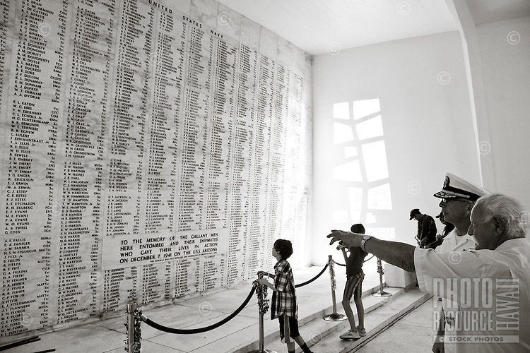 Children, senior man and a naval officer looking at the names of those who gave their lives at Pearl Harbor at the Arizona Memorial, Oahu