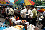An Office Executive having lunch during break at  a street food stall in Dalhousie area of Kolkata. Street food stalls are serving the office goers for decades. All kind of Indian foods are available on the street at an affordable price. They sale them openly. Street food stalls are another results of unempoloyment and over poppulation. They serve millions of people in India. Kolkata, West Bengal,  India  7/18/2007.  Arindam Mukherjee/Landov