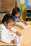 Education Preschool 4-5 year olds art activity two girls sitting side by side drawing with markers using opposite hands and tripod grips