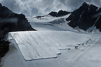 "A view from below shows how futile are the efforts of covering Brunnenkogel Ferner.  The glacier is wrapped with a fleece-like cover to keep it from melting. Covered ice melts slower. <br /> The ski area at 3,400 meters is covered to help save the ski industry since the glacier is retreating.  The cost of materials is one Euro per square meter.<br /> <br /> The Alpine glaciers -- in Austria, Switzerland, France and Italy -- are losing one percent of their mass every year and, even supposing no acceleration in that rate, will have all but disappeared by the end of the century. More hot, dry summers like that of 2003 in Europe, when the loss speeded to five percent, could cut the life expectancy to no more than 50 years, according to Wilfried Haeberli of the University of Zurich. ""We estimate that by the end of the 21st century, with a medium-type climate scenario, about five percent of what existed in the 1970s will have survived, he added."