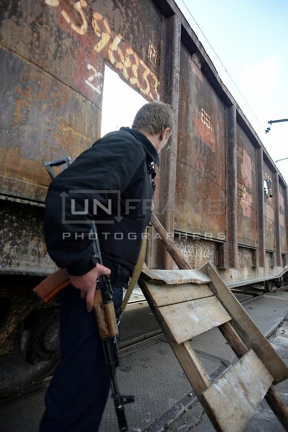 A Pro-Russian activist holding a machine gun at a railroad checkpoint. Slavyansk, Donetsk region.