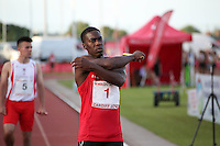 Tuesday 15th July 2014<br /> Pictured: Christian Malcolm<br /> RE: Welsh Sprinter Christian Malcolm stands on the track stretching his arms, holding a relay baton about to compete in the 4x100m relay at the Welsh Athletics International in the Cardiff International Sports Stadium South Wales, UK. His last race on home soil.