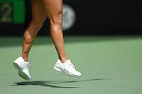Legs of a female tennis player in the air