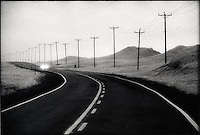 Solitary car driving along Telphone Poles lined Road<br />