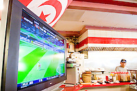 Tunisia fans watch their team play Ukraine in a World Cup match on June 23, 2006 at the Rock and Roll Cafe in New York City.  <br /> <br /> The World Cup, held every four years in different locales, is the world's pre-eminent sports tournament in the world's most popular sport, soccer (or football, as most of the world calls it).  Qualification for the World Cup is open to any country with a national team accredited by FIFA, world soccer's governing body. The first World Cup, organized by FIFA in response to the popularity of the first Olympic Games' soccer tournaments, was held in 1930 in Uruguay and was participated in by 13 nations.    <br /> <br /> As of 2010 there are 208 such teams.  The final field of the World Cup is narrowed down to 32 national teams in the three years preceding the tournament, with each region of the world allotted a specific number of spots.  <br /> <br /> The World Cup is the most widely regularly watched event in the world, with soccer teams being a source of national pride.  In most nations, the whole country is at a standstill when their team is playing in the tournament, everyone's eyes glued to their televisions or their ears to the radio, to see if their team will prevail.  While the United States in general is a conspicuous exception to the grip of World Cup fever there is one city that is a rather large exception to that rule.  In New York City, the most diverse city in a nation of immigrants, the melting pot that is America is on full display as fans of all nations gather in all possible venues to watch their teams and celebrate where they have come from.