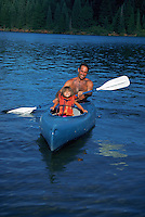 Father and daughter kayaking in lake