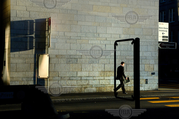 A businessman walks past a UBS building in Zurich's financial district. The Swiss banking industry holds an estimated 4,000 billion Swiss Francs (USD 4,240 billion) in assets, more than half of it foreign, including CHF 880 billion in undeclared European assets alone, benefiting from the country's famous banking secrecy laws.