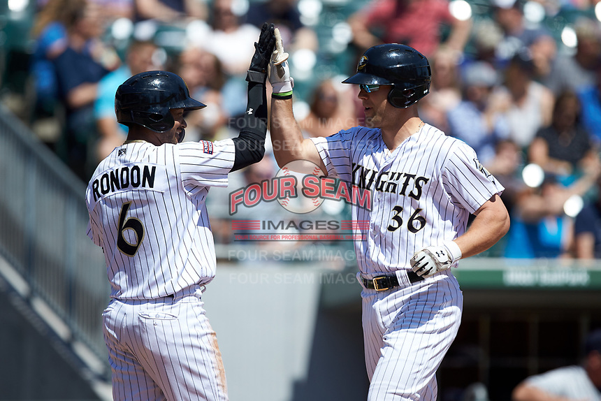 Kevan Smith (36) of the Charlotte Knights high fives teammate Jose Rondon (6) after hitting a home run against the Gwinnett Stripers at BB&T BallPark on May 2, 2018 in Charlotte, North Carolina.  The Knights defeated the Stripers 6-5.  (Brian Westerholt/Four Seam Images)