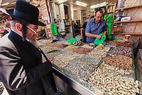Israel,Jerusalem, an orhodox jude man is choosing the food for the Shabbat in   the Mahane Yehuda Open Air Food Market,