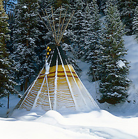 A colourful tepee half-buried by a fresh fall of snow against a backdrop of pine trees