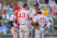 Hagerstown Suns pitching coach Sam Narron (43) has a meeting on the mound with his starting pitcher Jefry Rodriguez (21), catcher Craig Manuel (10) and second baseman Willie Medina (17) during the game against the Kannapolis Intimidators at CMC-Northeast Stadium on May 31, 2014 in Kannapolis, North Carolina.  The Intimidators defeated the Suns 4-3 in game two of a double-header.  (Brian Westerholt/Four Seam Images)