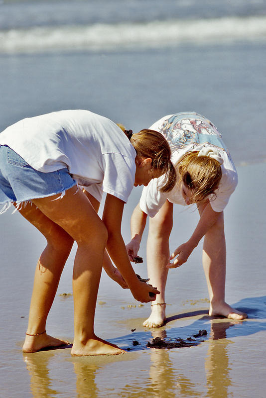 Teenage girls playing on beach. Near Yachats, Oregon.
