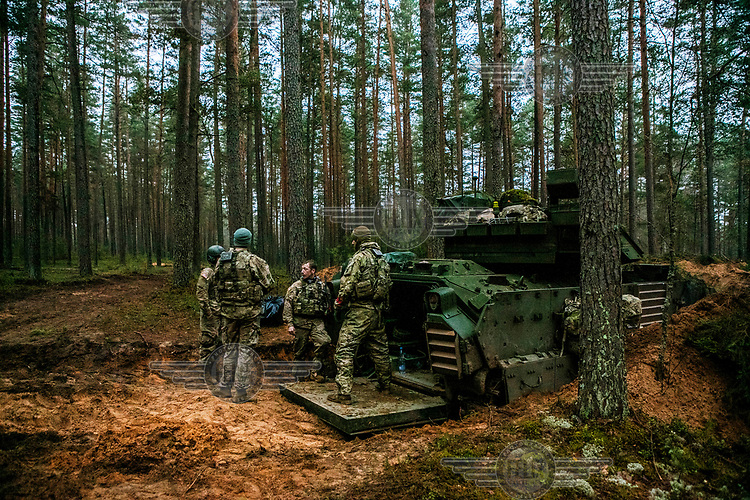 US Army soldiers rest after spending the night in a tank during NATO Iron Sword joint exercises.