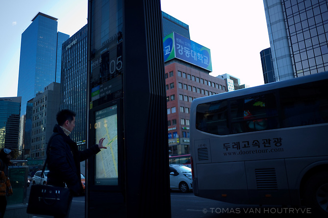 A pedestrian uses an outdoor touchscreen internet terminal in Gangnam, Seoul, South Korea, on Jan. 25, 2012. The terminals can search Google maps, send email, track nearby buses and other functions.