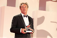 """VENICE, ITALY - SEPTEMBER 11: Director Paolo Sorrentino poses with the Silver Lion Grand Jury Prize for """"The Hand Of God"""" at the awards winner photocall during the 78th Venice International Film Festival on September 11, 2021 in Venice, Italy."""