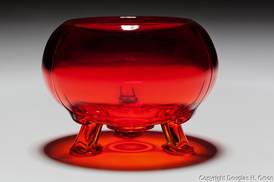 Looking into a red candy bowl, lying down with light from above, reflection and shadow on white graduated background.