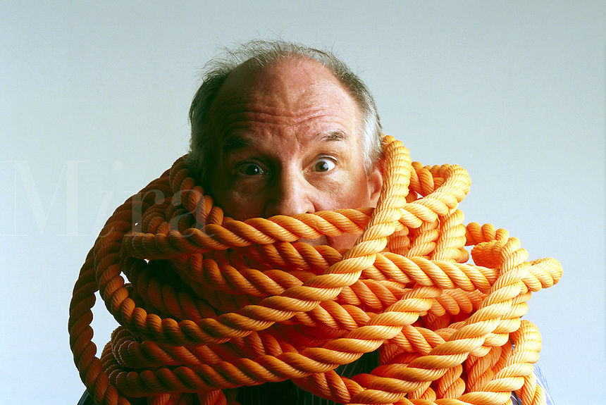 Rope around businessmans arms and neck
