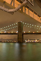 Available for Commercial and Editorial  Licensing Exclusively from Corbis.<br /> <br /> Please search for image # 42-20926519 at www.corbis.com<br /> <br /> Brooklyn Bridge and East River Illuminated at Night, Viewed from Esplanade under the F.D.R. Drive, New York City, New York State, USA