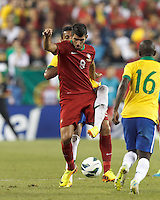 Under pressure, Portugal forward Nelson Oliveira (9) attempts to control the ball. In an international friendly, Brazil (yellow/blue) defeated Portugal (red), 3-1, at Gillette Stadium on September 10, 2013.