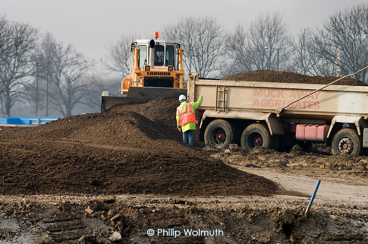 Construction workers with earth moving equipment at the Olympic Park site in Stratford.