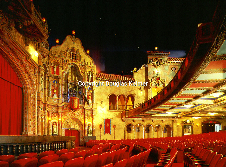 """The Rumanian-born Eberson is credited with devising the """"atmospheric"""" theater, in which the auditorium evoked an outdoor setting by means of a movie-set-like backdrop of facades beneath an artificial sky.  At the Tampa, whose generous construction budget was fueled by the Florida land boom of the early to mid 1920s, Eberson pulled out all the stops.  The Churrigueresque false fronts of his interior courtyard are draped in artificial foliage; here and there, stuffed birds perch on ledges, while projected clouds scud across a midnight-blue sky twinkling with constellations of electric """"stars"""".   The profusion of niches in the facades hold copies of classical busts and statuary ranging from Hermes to Christopher Columbus.  (Photo<br />©George Cott/Chroma Inc.; courtesy Tampa Theatre)"""
