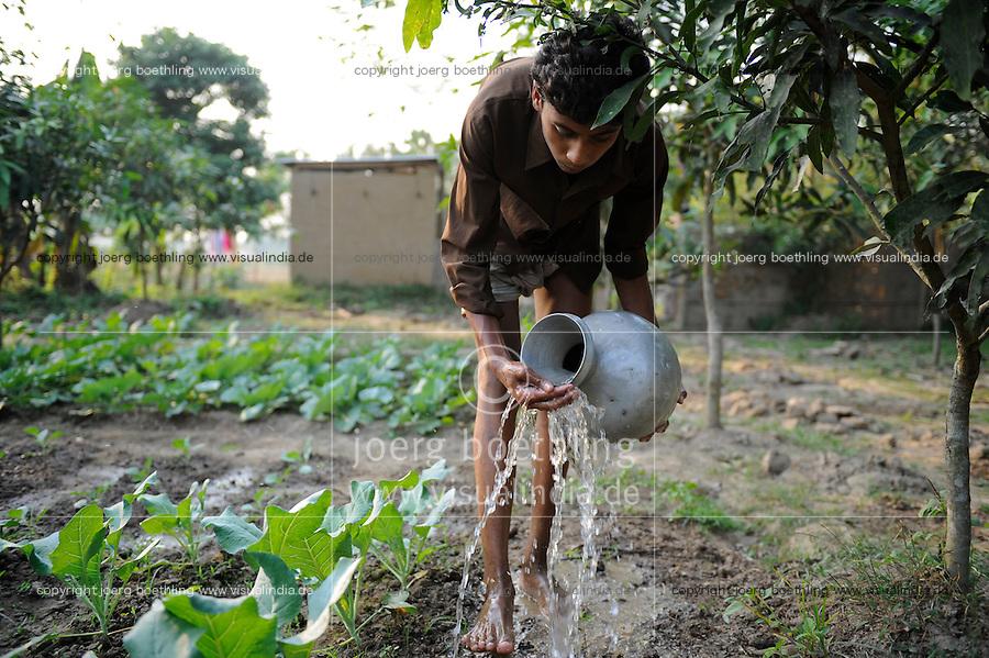 Bangladesh, Region Madhupur, Garo Jugendlicher bewaessert Gemuesegarten , Garos sind eine christliche u. ethnische Minderheit  / BANGLADESH Madhupur, Garo boy irrigate vegetables in garden, Garos is a ethnic group and mostly christians