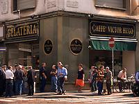 Men gather for Sunday morning conversation in front of Cafe Victor Hugo on Via Speronari in Milan Ital