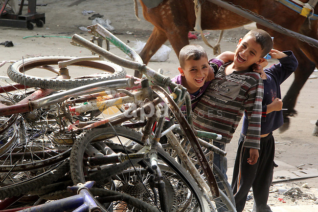 Palestinian children play next to old bicycles in front of a workshop of Khamis al-Burdini, 15, as he repairs bicycles in Gaza city, on March 13, 2013. al-Burdini opened his workshop 3 years ago after leaving his school to provide his poor family. Photo by Ezz al-Zanoon