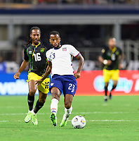DALLAS, TX - JULY 25: Kellyn Acosta #23 of the United States passes the ball in front of Daniel Johnson #16 of Jamaica during a game between Jamaica and USMNT at AT&T Stadium on July 25, 2021 in Dallas, Texas.