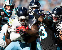 CHARLOTTE, NC - NOVEMBER 3: Derrick Henry #22 of the Tennessee Titans is tackled by Tre Boston #33 of the Carolina Panthers during a game between Tennessee Titans and Carolina Panthers at Bank of America Stadium on November 3, 2019 in Charlotte, North Carolina.
