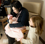 WATERBURY, CT- 01 JAN 2008- 010108JT08-<br /> Andrea Murtishi, of Waterbury, wraps her new daughter, Avery Charlize, in a blanket as her other daughter Aryanna, 2, watches in Andrea's hospital room at Waterbury Hospital on Tuesday, New Year's Day. Avery Charlize was born at 1:11 a.m. New Year's Day. In the background is Tyler Murtishi, 6.<br /> Josalee Thrift / Republican-American
