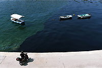 """Pictured: The oil spill moving slowly towards the coast of Salamina, Greece<br /> Re: An oil spill off Salamina island's eastern coast is spreading and has become """"an environmental disaster"""" according to local authorities in Greece.<br /> The spill was caused by the sinking of the Aghia Zoni II tanker, carrying 2,200 metric tons of fuel oil and 370 metric tons of marine gas oil on Saturday, southwest of the islet of Atalanti near Psytalleia. According to reports, the coastline stretching from Kinosoura to the Selinia community has """"turned black"""" and authorities fear a new leak from the sunken ship.<br /> According to the island's mayor, Isidora Papathanasiou, the weather """"turned on Sunday afternoon and brought the oil spill to Salamina."""""""