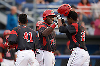 Batavia Muckdogs Lazaro Alonso (19), fist bumps Thomas Jones (49) after hitting a home run during a game against the Mahoning Valley Scrappers on August 29, 2017 at Dwyer Stadium in Batavia, New York.  Brayan Hernandez (41) is at left.  Batavia defeated Mahoning Valley 2-0.  (Mike Janes/Four Seam Images)