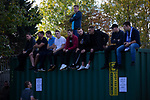 Spectators sitting on a shipping container watching the first-half at the UTS Stadium during the FA Cup fourth qualifying round match between Dunston UTS (in blue) and their local rivals Gateshead. Founded in 1975, the home team were formerly known as Dunston Federation. The visitors won 4-0 watched by a record crowd of 2,500.
