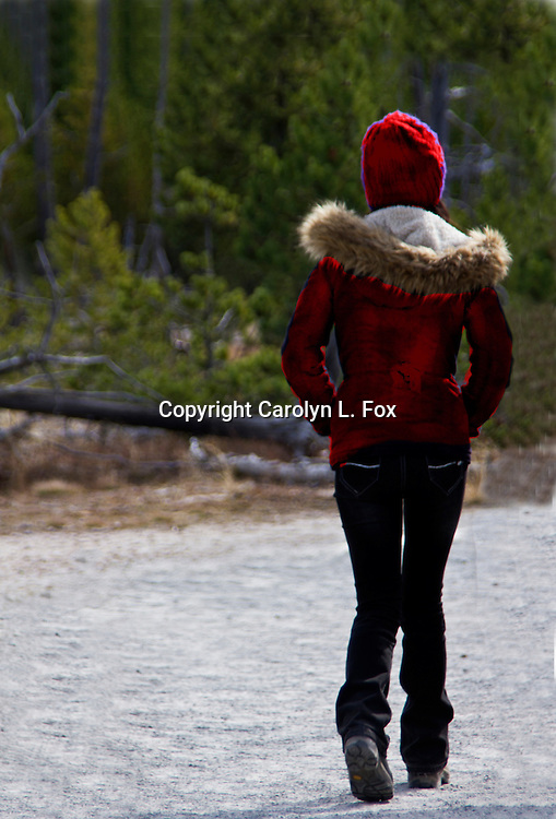 A womna wearing a red coat and stocking hat walks towards the woods.