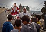 Palestinian youths look at a man dressed as Jesus sitting on a donkey as Christian pilgrims celebrate Palm Sunday in Jerusalem Sunday, April 13 2014. Photo by Eyal Warshavsky