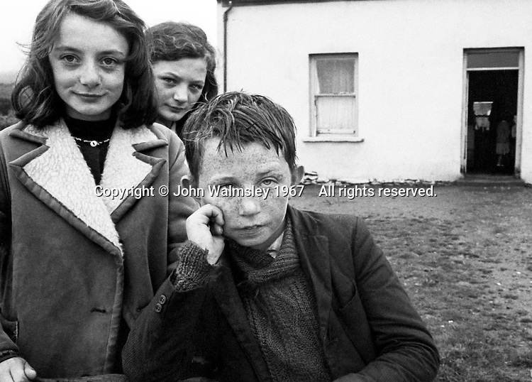 """Three kids and their home, Dunquin (in Gaelic, Dún Chaoin, meaning """"Caon's stronghold""""), on the tip of the Dingle Peninsula, County Kerry, Ireland.  1967."""