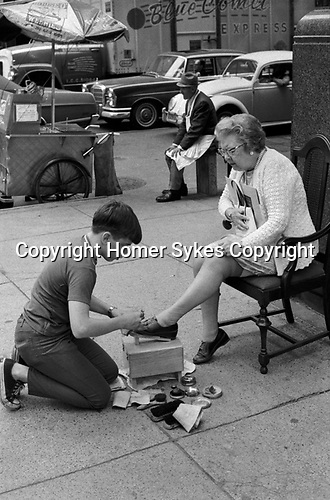 Shoeshine boy 1970s US. Teenager working making extra pin money being a shoe shine boy, polishing a customers, an older womans leather shoes. Manhattan, New York 1972 USA