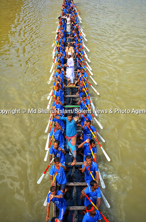 Pictured: Dozens of rowers sit shoudler to shoulder along the length of the boat as they compete in a boat race known locally as 'Nouka Baich' down the Ghaghat River in Gaibandha district, Bangladesh. <br /> <br /> The long thin boats, which are between 70 feet to 120 feet long, can reach speeds of around 20 mph and each boat can hold 80 to 100 people. <br /> <br /> Thousands of locals line the river bank to watch the traditional boat race in Bangladesh, and the winners of the races are given various prizes including cash, televisions, cows, buffaloes and even goats.<br /> <br /> Please byline: Md Shafiul Islam/Solent News<br /> <br /> © Md Shafiul Islam/Solent News & Photo Agency<br /> UK +44 (0) 2380 458800