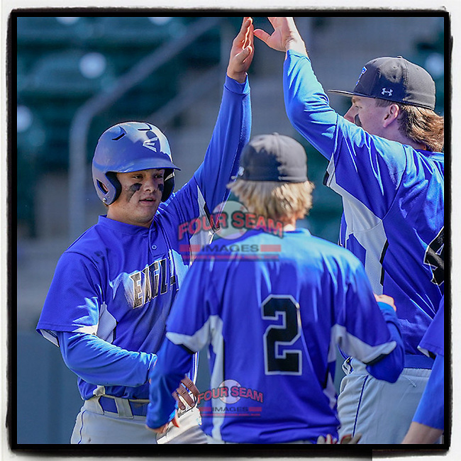 Blake Shirley (6) of the Eastside High School Eagles, left, is greeted after scoring the go-ahead run in a 6-5 win over the Wren High School Hurricanes on Saturday, March 20, 2021, at Fluor Field at the West End in Greenville, South Carolina. (Tom Priddy/Four Seam Images)