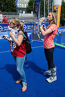 12 JUL 2014 - HAMBURG, GER - Non Stanford (right), still wearing the protective boot to aid her recovery from a stress injury in her foot, waits to be interviewed for a television programme before the elite women's 2014 ITU World Triathlon Series round in Hamburg, Germany (PHOTO COPYRIGHT © 2014 NIGEL FARROW, ALL RIGHTS RESERVED)