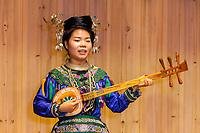 Zhaoxing, Guizhou, China.  Young Woman of the Dong Ethnic Minority Playing a Five-stringed Lute (pipa).