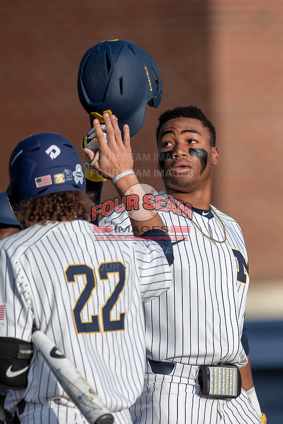 Michigan Wolverines outfielder Jordan Nwogu (42) is greeted at the plate by Jordan Brewer (22) after hitting a home run during the NCAA baseball game against the Eastern Michigan Eagles on May 8, 2019 at Ray Fisher Stadium in Ann Arbor, Michigan. Michigan defeated Eastern Michigan 10-1. (Andrew Woolley/Four Seam Images)