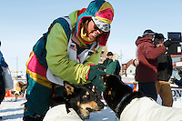 Monica Zappa Congratulates her dogs at the finish line in Nome on Saturday March 21, 2015 during Iditarod 2015.  <br /> <br /> (C) Jeff Schultz/SchultzPhoto.com - ALL RIGHTS RESERVED<br />  DUPLICATION  PROHIBITED  WITHOUT  PERMISSION