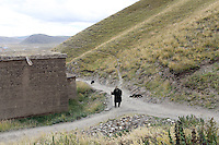 A pilgrim in the town of Sershul on the Tibetan Plateau, in western China. The town is home to a large monastery which houses thousands of monks. The Sanjiangyuan or Three Rivers Headwater region of western China contains the sources of the Yangtze, Mekong and Yellow Rivers.