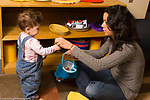 Day Care Center female caregiver interacting with young toddler